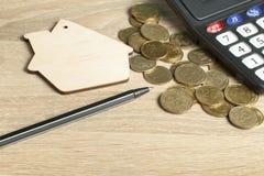 Концепция домашних сбережений, бюджета, финансовых и свойства Модель дома, калькулятора и монеток на деревянной таблице офиса Стоковое фото RF