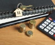 Концепция домашних сбережений, бюджета, финансовых и свойства Модель дома, ключей, калькулятора и монеток на деревянной таблице о Стоковое фото RF