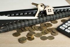 Концепция домашних сбережений, бюджета, финансовых и свойства Модельный дом, ключи, калькулятор и монетки на деревянной таблице о Стоковые Изображения RF