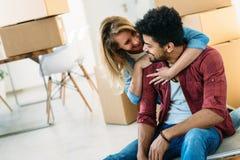 Концепция дома, людей, двигать и недвижимости - счастливая пара имея потеху пока двигающ внутри стоковое фото