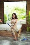 Концепция домоустройства Женщина отправляя СМС пока делающ домашнее хозяйство стоковые фотографии rf