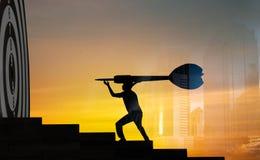 Концепция достижения и цели, силуэт удерживания бизнесмена стоковое изображение