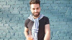Концепция еды и городской жизни улицы Молодой усмехаясь бородатый человек держа чашку с smoothies или лимонадом сока напитка сток-видео