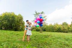 Концепция летних отпусков, торжества и датировка - пара с красочными воздушными шарами в природе стоковое изображение rf