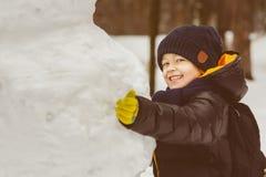 Концепция деятельностей при зимы Счастливый мальчик стоя рядом с снеговиком внешним Стоковое фото RF