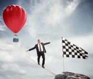 Концепция дела бизнесмена которое преодолевает проблемы достигая флаг на веревочке стоковое изображение