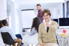 Концепция дела, запуска и людей - счастливая творческая команда говоря в офисе Стоковое Изображение RF
