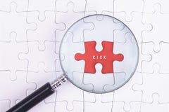 Концепция дела - стекло увеличителя на белом puzze с словом РИСКА Стоковые Фото