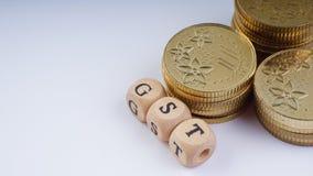 Концепция дела с словом GST на штабелированных монетках Стоковое Изображение