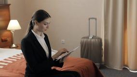 Концепция дела, технологии, интернета и гостиницы - счастливая молодая коммерсантка при компьютер ПК таблетки лежа в гостинице вн акции видеоматериалы