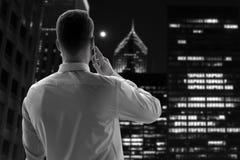 Концепция дела, людей и офиса - бизнесмен вызывая на умном телефоне над офисом близко с окном в ноче стоковое фото