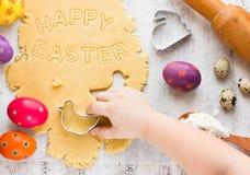 Концепция еды пасхи Руки ребенк отрезали печенье от сырцового теста на белой таблице Стоковое Фото