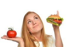 Концепция еды фаст-фуда сравнивая сандвич бургера в руке и t Стоковая Фотография