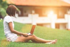 Концепция женщины онлайн ходя по магазинам Женщина в зеленом парке с современным ноутбуком Остров Бали стоковые изображения