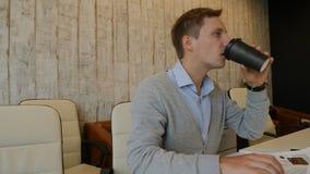 Концепция жизни офиса Молодой мужской работник сидит печатать ПК Выпивает кофе от бумажного стаканчика brainwaves Снятый в 4 k сток-видео