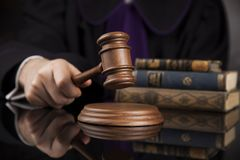 Концепция закона, мужской судья в зале судебных заседаний поражая молоток стоковое фото rf