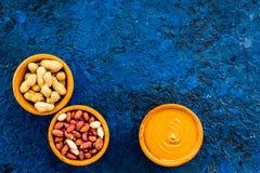 Концепция затира арахиса Шары с маслом, гайки в раковине, слезли гайки на голубом космосе экземпляра взгляд сверху предпосылки Стоковое Изображение RF