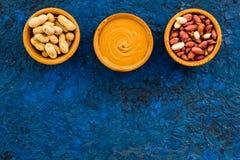 Концепция затира арахиса Шары с маслом, гайки в раковине, слезли гайки на голубом космосе экземпляра взгляд сверху предпосылки Стоковая Фотография
