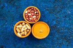 Концепция затира арахиса Шары с маслом, гайки в раковине, слезли гайки на голубом космосе экземпляра взгляд сверху предпосылки Стоковая Фотография RF