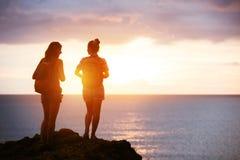 Концепция захода солнца моря перемещения 2 девушек Стоковое Изображение RF