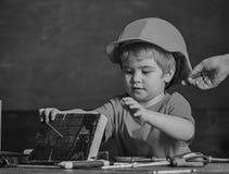 Концепция защиты и безопасности Тщательно защитите ребенк с шлемом Малыш в защитном шлеме на мастерской Ребенок милый стоковая фотография