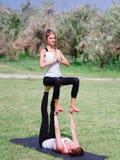 Концепция здорового образа жизни 2 женщины делая йогу в парке Стоковые Изображения