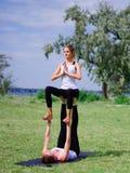 Концепция здорового образа жизни 2 женщины делая йогу в парке Стоковые Фото