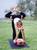 Концепция здорового образа жизни 2 женщины делая йогу в парке Стоковая Фотография