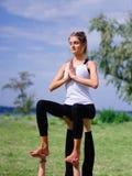 Концепция здорового образа жизни 2 женщины делая йогу в парке Стоковые Изображения RF