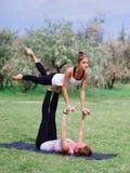 Концепция здорового образа жизни 2 женщины делая йогу в парке Стоковое фото RF