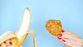 Концепция здоровой и нездоровой еды банан против зажаренной обвалянной в сухарях куриной ножки на яркой голубой предпосылке женск стоковая фотография rf