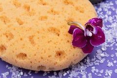 Концепция здоровья спа Естественные ванна пены & губка моря ливня, цветок орхидеи и соль Epsom лаванды на ярком пурпуре стоковые фото