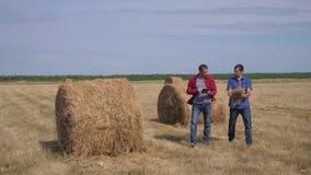 Концепция земледелия сыгранности умная обрабатывая землю 2 работника фермеров людей изучая стог сена в поле на цифровом планшете видеоматериал