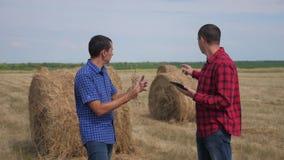Концепция земледелия сыгранности умная обрабатывая землю 2 работника фермеров людей изучая стог сена в поле на образе жизни цифро акции видеоматериалы