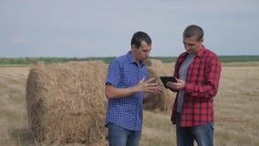 Концепция земледелия сыгранности умная обрабатывая землю 2 работника фермеров людей изучая стог сена в поле на цифровом планшете акции видеоматериалы