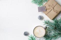 Концепция зимы, подарок рождества, кружка кофе, конусы сосны и Braches, уютная предпосылка натюрморта стоковое фото rf