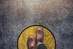 Концепция зоны комфорта, мужчина с кожаными ботинками шагает над кругом стоковая фотография