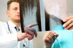 Концепция здравоохранения, медицинских и радиологии - мужские доктора смотря рентгеновский снимок ноги Стоковое фото RF