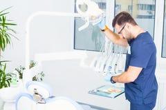 Концепция здравоохранения, профессии, стоматологии и медицины - мужской дантист над медицинской предпосылкой офиса Стоковое фото RF