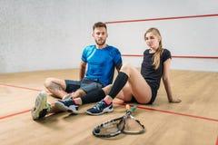 Концепция игры сквоша, молодая пара, ракетки, шарик стоковое фото