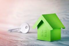 Концепция имущества, ключ и бумажный дом с окнами эскиза на светлой деревянной предпосылке Концепция имущества идеи по-настоящему стоковое изображение
