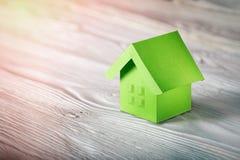 Концепция имущества, ключ и бумажный дом с окнами эскиза на светлой деревянной предпосылке Концепция имущества идеи по-настоящему стоковые фото