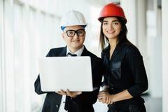 Концепция инженерства и архитектуры Инженеры работая на строительной площадке держа компьтер-книжку, человека архитектора работая Стоковое фото RF