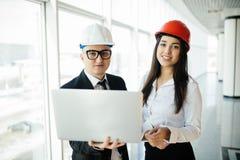 Концепция инженерства и архитектуры Инженеры работая на строительной площадке держа компьтер-книжку, человека архитектора работая Стоковое Фото