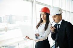 Концепция инженерства и архитектуры Инженеры работая на строительной площадке держа компьтер-книжку, человека архитектора работая Стоковая Фотография