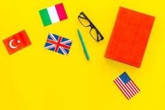 Концепция исследования языка Учебники или словари иностранного языка близко сигнализируют на желтом космосе экземпляра взгляд све стоковое изображение