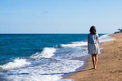 Концепция каникул - задний взгляд женщины идя на bea захода солнца Стоковая Фотография RF
