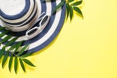 Концепция каникул перемещения лета Striped шляпа и солнечные очки на желтом цвете стоковая фотография