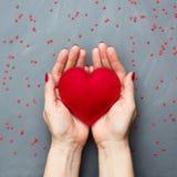 Концепция карточки ` s валентинки с сладостными красными сердцами в руке на серой предпосылке скопируйте космос над взглядом Стоковое фото RF
