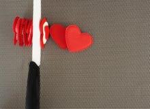 Концепция Керамический нож режет красные валентинки сердец Стоковая Фотография